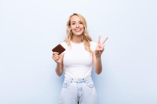 財布を持ってピースサインをする人の画像
