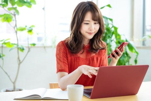 PCをいじる女性の画像
